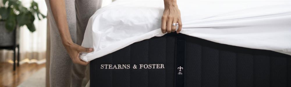 Woman putting sheets on a Stearns & Foster® mattress